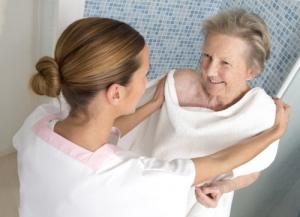 elderly woman taking a bath with her caretaker